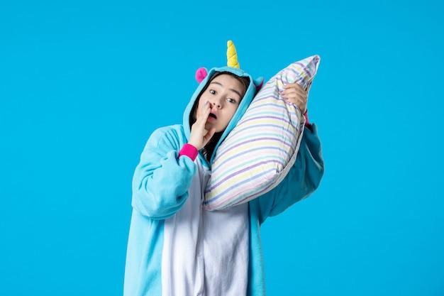 正面図青い背景に枕を抱き締めるパジャマパーティーの若い女性遅いベッドの女性楽しい夢のゲーム睡眠悪夢夜休みささやき