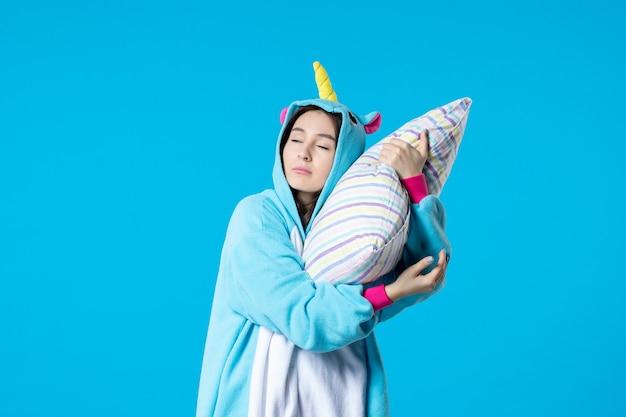 파란색 배경에 베개를 들고 잠옷 파티를 위해 잠옷을 입은 젊은 여성 늦은 침대 여자 꿈 게임 수면 악몽 밤 휴식