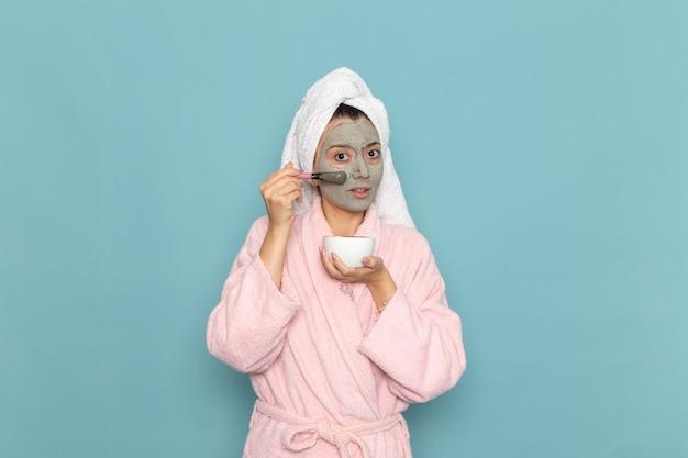 Вид спереди молодая женщина в розовом халате после душа, наносящая крем на синюю стену, косметическая вода, чистка в душе
