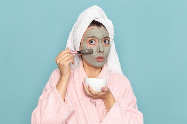 Вид спереди молодая женщина в розовом халате после душа, наносящая крем на голубую стену, косметическая вода, чистка в душе