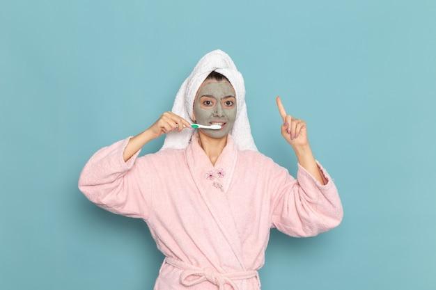 Вид спереди молодая женщина в розовом халате после душа, чистящая зубы на синей стене, чистящая красота чистой водой, крем для ухода за собой, душ