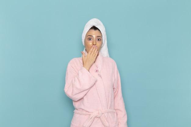 Вид спереди молодая женщина в розовом халате после душа, прикрывая рот на голубой стене, косметическая вода, чистка в душе