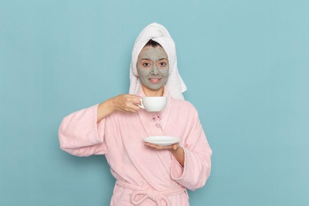青い壁のクリーニング美容きれいな水セルフケアクリームシャワーで笑顔でコーヒーを飲むシャワーの後のピンクのバスローブの正面図
