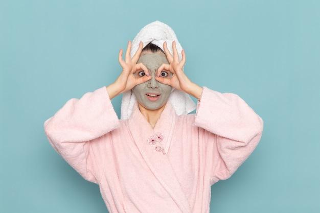 Вид спереди молодая женщина в розовом халате после душа, смешно позирует на синей стене, чистка красоты, чистая вода, крем для ухода за собой, душ