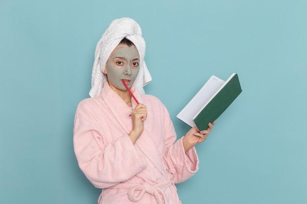 Вид спереди молодая женщина в розовом халате после душа, держащая тетрадь на синей стене, косметический крем с водой, самообслуживание, душ, ванная комната