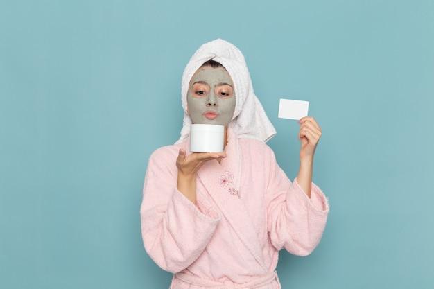 파란색 벽 아름다움 물 크림 셀프 케어 샤워 욕실에 크림과 카드를 들고 샤워 후 분홍색 목욕 가운에 전면보기 젊은 여성