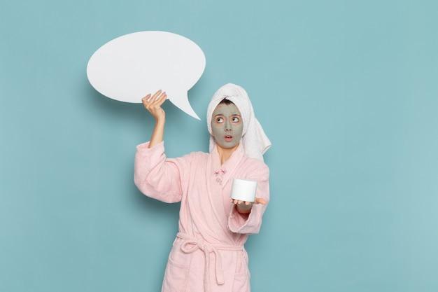 Вид спереди молодая женщина в розовом халате после душа, держащая крем и знак на синей стене, косметический водный крем, ванная комната с душем