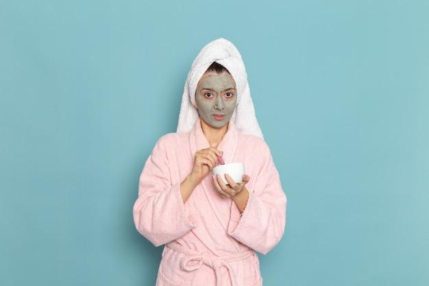 Вид спереди молодая женщина в розовом халате после душа, держащая крем на синей стене, чистка красоты, чистая вода, крем для ухода за собой, душ