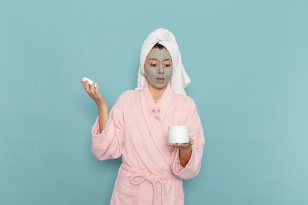 Вид спереди молодая женщина в розовом халате после душа, держащая крем на синей стене, косметическая водяная ванна, крем для душа, ванная комната