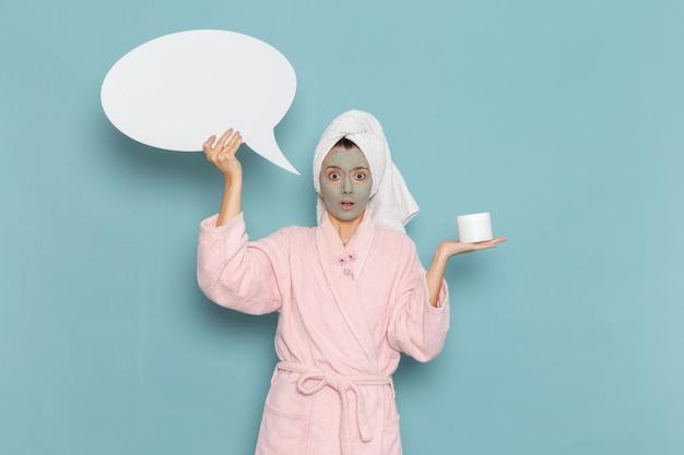 Вид спереди молодая женщина в розовом халате после душа держит огромный знак на синей стене, косметический водный крем, душевая кабина для самообслуживания
