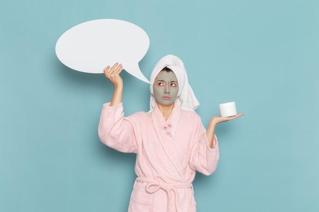 Вид спереди молодая женщина в розовом халате после душа держит огромный белый знак на синей стене, косметический водный крем, душевая кабина для самообслуживания