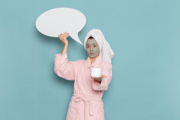 Вид спереди молодая женщина в розовом халате после душа, держащая огромный белый знак на голубой стене, косметический водный крем для душа в ванной комнате