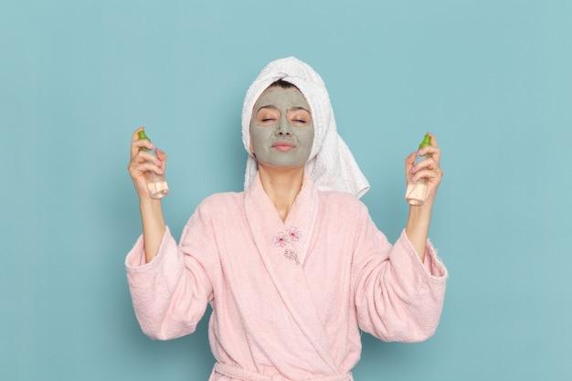 Вид спереди молодая женщина в розовом халате после душа, держащая средства для снятия макияжа на синей стене, косметический водный крем, душ для самообслуживания