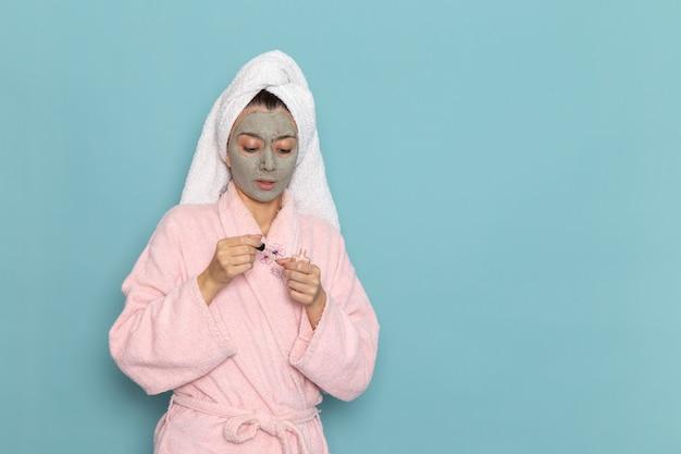 Вид спереди молодая женщина в розовом халате после душа, держащая лак для ногтей на синем столе, косметический водный крем в душе по уходу за собой