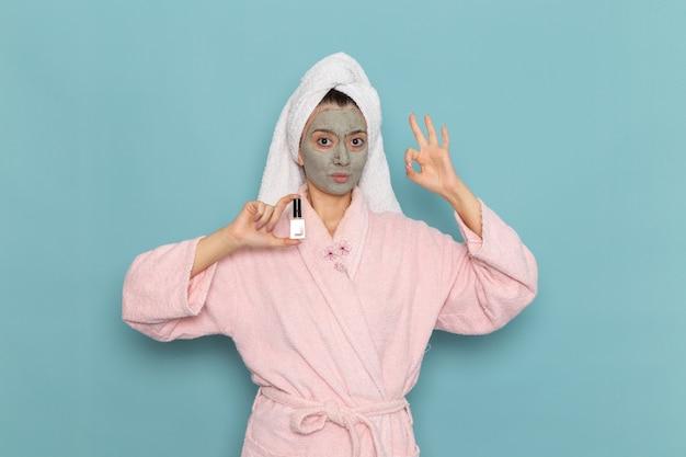 Вид спереди молодой женщины в розовом халате после душа, держащей лак для ногтей на синей стене, красота чистой воды в душе по уходу за собой