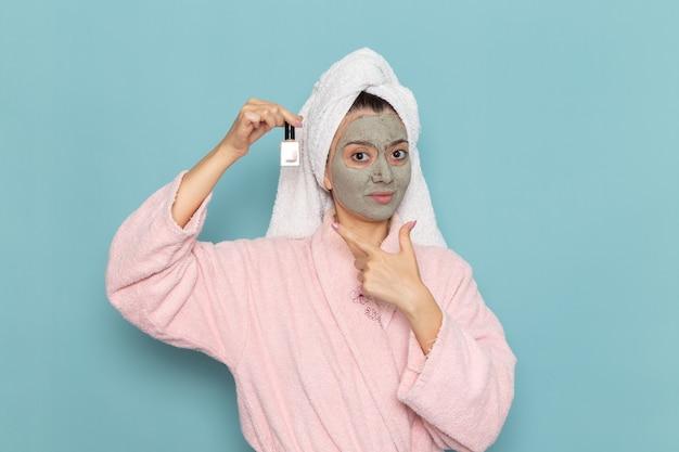 Вид спереди молодая женщина в розовом халате после душа, держащая лак для ногтей на синей стене, чистящая красота чистой водой, крем для ухода за собой, душ