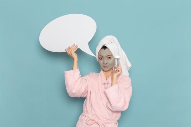 Вид спереди молодая женщина в розовом халате после душа, держащая знак и спрей на синей стене, косметический водный крем для душа, ванной комнаты