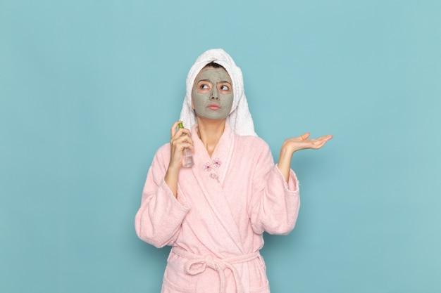 Вид спереди молодая женщина в розовом халате после душа держит спрей на синей стене, чистка красоты, чистая вода, крем для ухода за собой, душ
