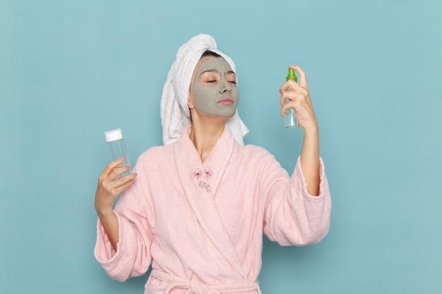 Вид спереди молодая женщина в розовом халате после душа держит спреи на синей стене, крем для водяной ванны красоты, душ для ухода за собой