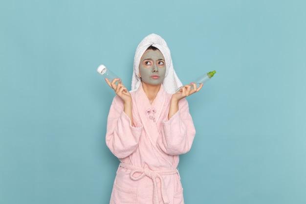 Вид спереди молодая женщина в розовом халате после душа, держащая спреи на синей стене, косметический водный крем, душевая кабина для самообслуживания