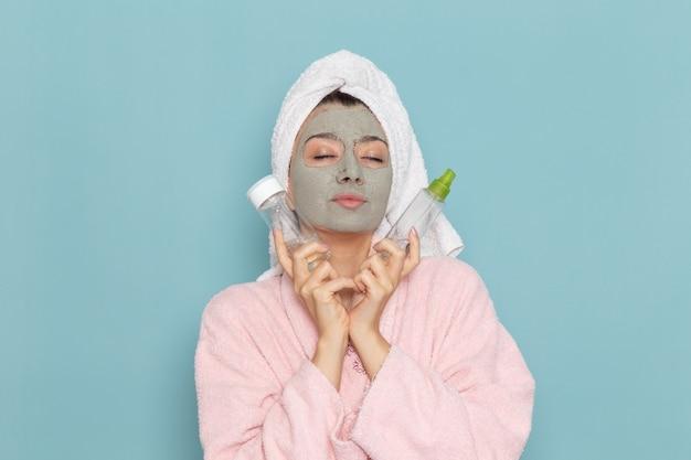 Вид спереди молодая женщина в розовом халате после душа, держащая спреи на голубой стене, косметический водный крем для душа, ванной комнаты