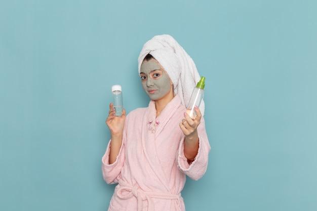 Вид спереди молодая женщина в розовом халате после душа, держащая спреи на синей стене, косметический водный крем, душ для ухода за собой