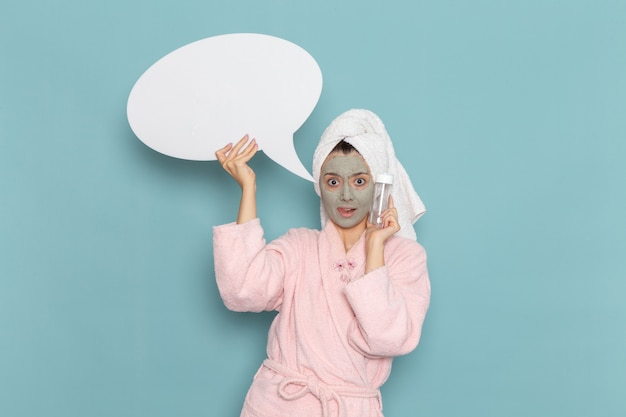 Вид спереди молодая женщина в розовом халате после душа, держащая белый знак и спрей на синей стене, косметический водный крем, душ для ухода за собой