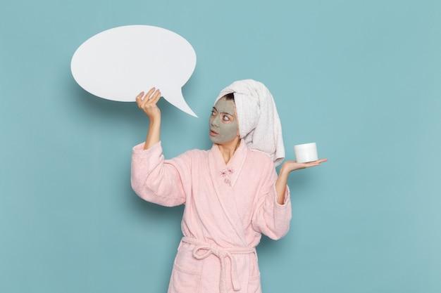 Вид спереди молодая женщина в розовом халате после душа держит белый знак на синей стене, крем для водяной ванны красоты, душ для ухода за собой