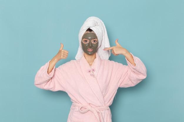 青い机の上のシャワーの後のピンクのバスローブの正面図若い女性美容水バスクリームセルフケアシャワー