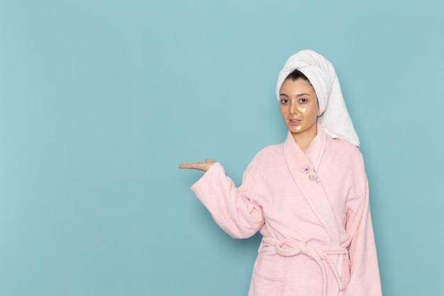 Вид спереди молодая женщина в розовом халате после душа на синей стене, косметическая водяная ванна, крем для душа