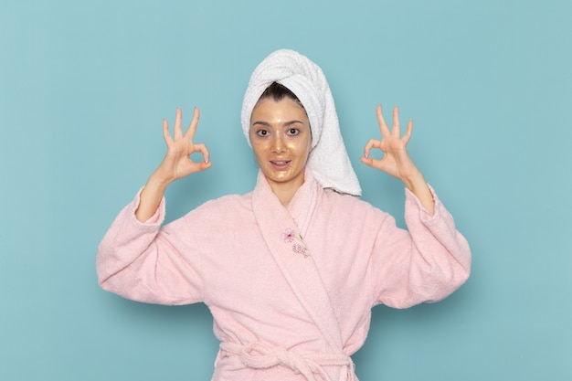 青い壁のクリーニング美容きれいな水セルフケアクリームシャワーのシャワーの後のピンクのバスローブの正面図若い女性