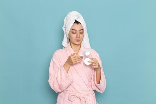 水色の壁のクリーニングの美しさのきれいな水セルフケアクリームシャワーのシャワーの後のピンクのバスローブの正面図若い女性