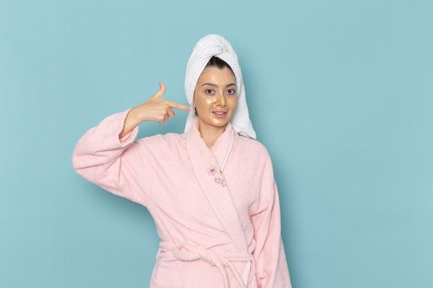 青い壁のクリーニング美容きれいな水セルフケアクリームシャワーでポーズをとってシャワーを浴びた後のピンクのバスローブの正面図若い女性