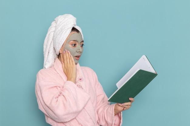 Вид спереди молодая женщина в розовом халате после душа читает зеленую тетрадь на синей стене, косметический водный крем, душевая кабина для самообслуживания