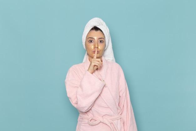 Вид спереди молодая женщина в розовом халате после душа, показывающая тихий знак на синей стене, косметический водный крем, душевая, ванная комната