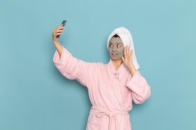 Вид спереди молодая женщина в розовом халате после душа, делающая селфи на синей стене, косметический водный крем, душ самообслуживания