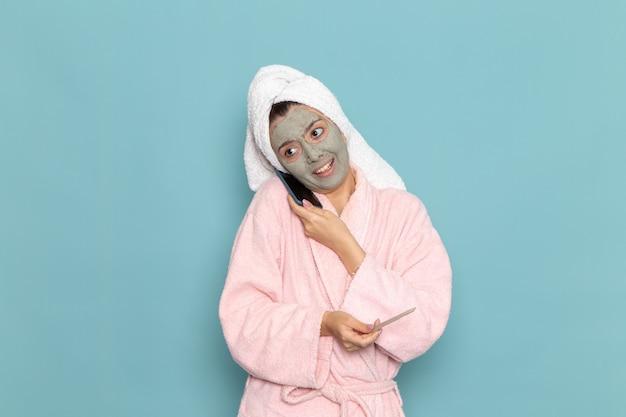 Вид спереди молодая женщина в розовом халате после душа разговаривает на синей стене, красота, чистая вода, крем для ухода за собой, душ