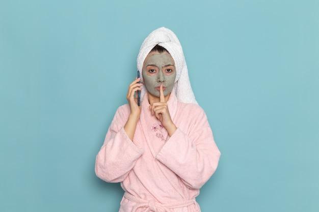 Вид спереди молодая женщина в розовом халате после душа разговаривает по телефону на синей стене, красотка, чистая вода, крем для ухода за собой, душ