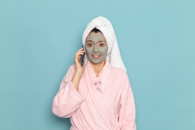 青い壁のクリーニング美容きれいな水セルフケアクリームシャワーで電話で話しているシャワーの後のピンクのバスローブの正面図若い女性