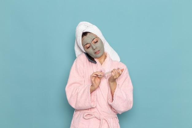 Вид спереди молодая женщина в розовом халате после душа разговаривает по телефону на голубом столе, вода красоты, уход за собой, душ, чистый