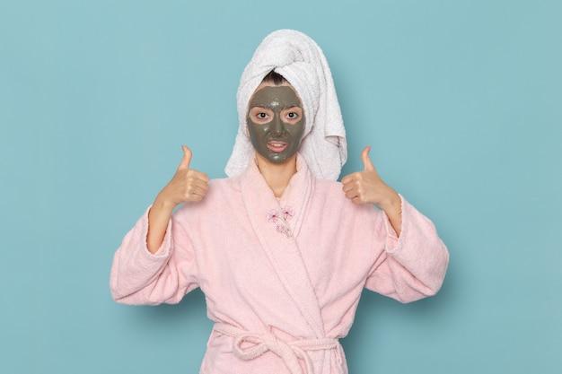 青い机の上の彼女の顔に暗いマスクとシャワーの後のピンクのバスローブの正面図若い女性美容ウォータークリームセルフケアシャワーバスルーム