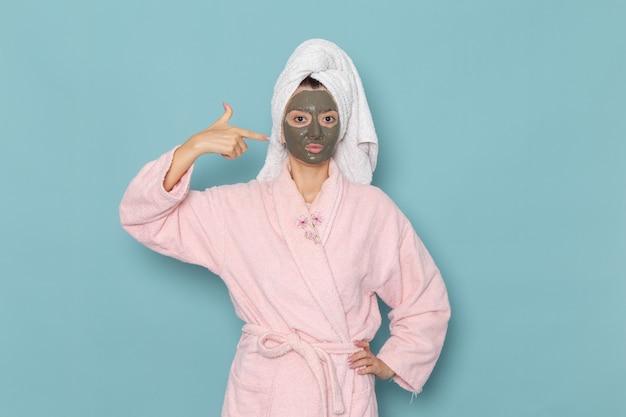 Вид спереди молодая женщина в розовом халате после душа с темной маской на лице на синей стене косметический водный крем для душа в ванной комнате
