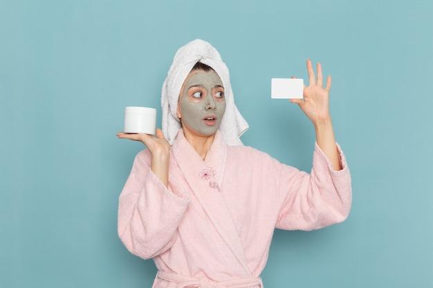 正面図ピンクのバスローブを着た若い女性がシャワーを浴びた後、青い壁にカードを持っている彼女の顔にマスクを付けてシャワークリーニング美容セルフケアクリーム