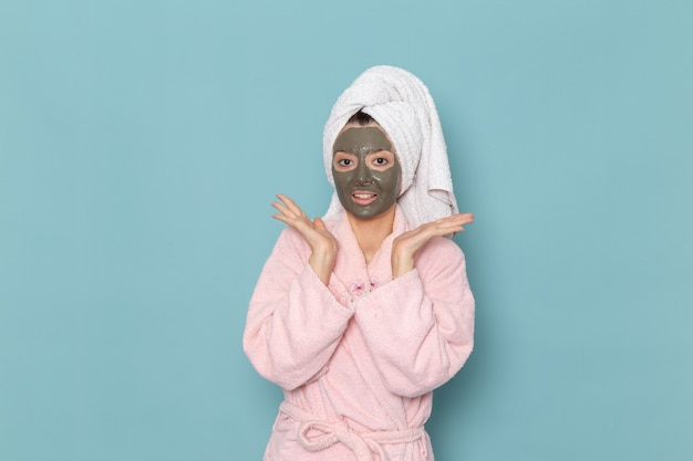 青い壁の美しさのウォータークリームセルフケアシャワーバスルームに笑顔のマスクとシャワーの後のピンクのバスローブの正面図若い女性