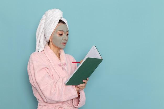 Вид спереди молодая женщина в розовом халате после душа пишет на синей стене косметический водный крем для душа в ванной комнате