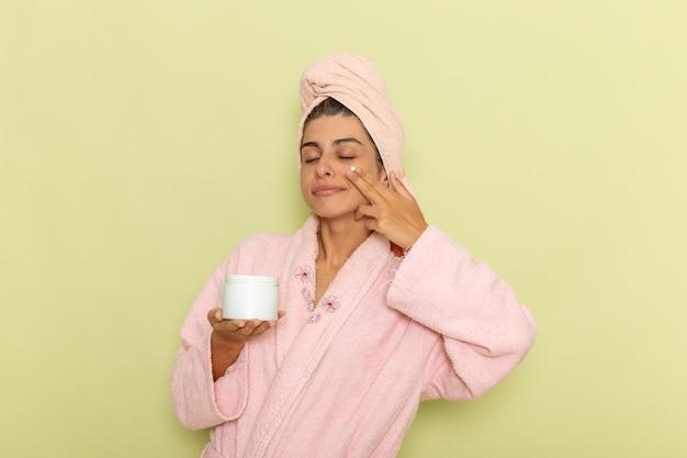 Вид спереди молодая женщина в розовом халате, наносящая крем для лица на зеленую поверхность