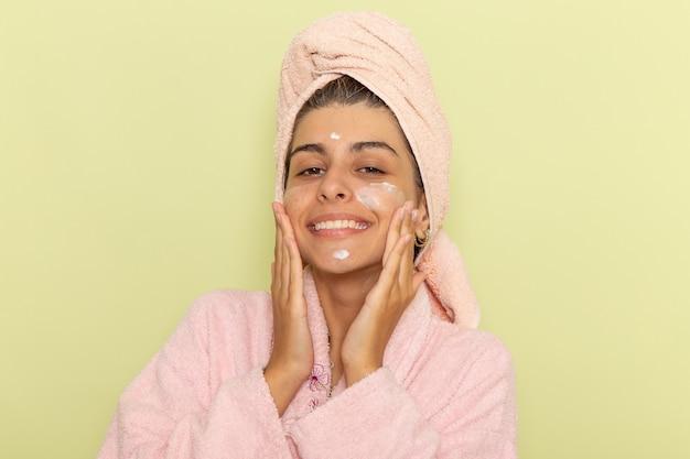 Вид спереди молодая женщина в розовом халате, наносящая крем для лица на светло-зеленую поверхность