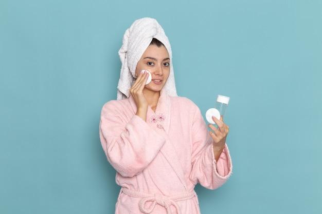 ピンクのバスローブを着た若い女性の正面図青い机の上のメイクから顔を掃除美容セルフケアクリームシャワーを掃除