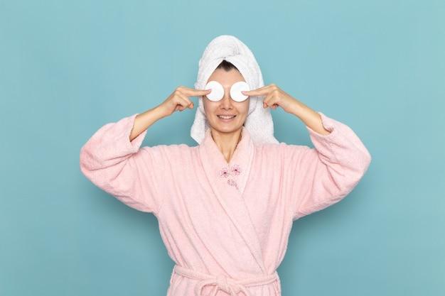 ピンクのバスローブを着た若い女性が青い壁に小さな綿で目を覆っている正面図シャワークリーニング美容セルフケアクリーム