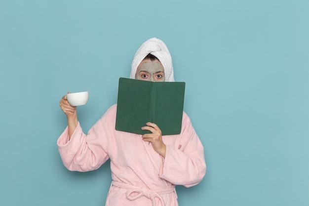 ピンクのバスローブを着た若い女性がコーヒーを飲み、水色の壁のクリーニング美容セルフケアクリームシャワーでコピーブックを読んでいる正面図